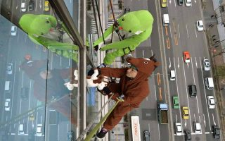 Workers clad in snake (top) and horse (bottom) costumes, to represent the outgoing Year of the Snake and incoming Year of the Horse, clean windows some 55 meters (180 ft.) above the ground on the side of a hotel in Tokyo on December 18, 2013. The hotel sponsored the event to promote the Yaesu business district near Tokyo Station ahead of New Year's Day, one of Japan's biggest holidays of the year.     AFP PHOTO / KAZUHIRO NOGI