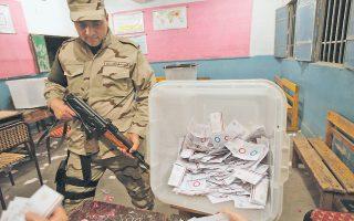 Ενας Αιγύπτιος στρατιώτης φυλάσσει τον χώρο, καθώς οι αρμόδιοι καταμετρούν τις ψήφους μετά το κλείσιμο των καλπών του δημοψηφίσματος για την εγκαθίδρυση νέου Συντάγματος στην Αίγυπτο.