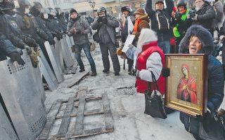 Εικόνα της Θεομήτορος κρατά η διαδηλώτρια αυτή μπροστά στους απαθείς άνδρες των ειδικών δυνάμεων της αστυνομίας στο κέντρο του Κιέβου.
