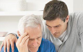 Eνας γιος κρατάει στοργικά τον πατέρα του που πάσχει από Αλτσχάιμερ.
