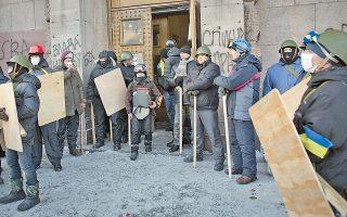 Διαδηλωτές, οπλισμένοι με ξύλινα κοντάρια και ασπίδες, παρατάσσονται έξω από ένα κτίριο, στο κέντρο του Κιέβου, ενώ στο Κοινοβούλιο συζητείται το ενδεχόμενο χορήγησης αμνηστίας στους συλληφθέντες ακτιβιστές.