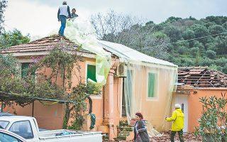 Κάτοικοι καλύπτουν τη στέγη του σπιτιού, τμήμα της οποίας κατέρρευσε μετά τον μεγάλο σεισμό της Κυριακής.