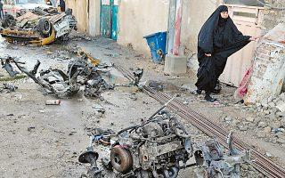 Μια γυναίκα διασχίζει το σημείο όπου εξερράγη ένα όχημα με εκρηκτικό μηχανισμό, στη συνοικία Σούλα της Βαγδάτης.