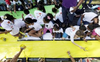 Children paint during a Guinness World Record event as part of celebrations for the 100-year-anniversary of the Panama Canal in Panama City January 18, 2014. According to a representative from the Guinness World Records, the event, which was organised by the Panama Canal Authority and the Olga Sinclair Foundation, broke the Guinness World Record with 5,084 children painting a massive mural together at the same time for three minutes. REUTERS/Carlos Jasso (PANAMA - Tags: SOCIETY ANNIVERSARY)