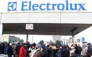 epa04045599 Electrolux workers are pictured during a protest outside the factory in Porcia di Pordenone, Italy, 28 January 2014. Swedish home appliances multinational Electrolux was facing criticism in Italy on 28 January over a plan to cut workers' salaries in order to put off the possibility of moving its operations to Eastern Europe, where labour is cheaper.  EPA/STEFANO LANCIA