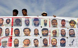 Υεμενίτες κρατούν πανώ με τα πρόσωπα των φυλακισμένων συμπατριωτών τους στο Γκουαντανάμο (Photo: EPA/YAHYA ARHAB)