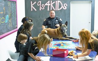 In this Feb. 18, 2013 photo provided by K9s4KIDS, Harris County Sheriff's Deputy John Palermo and his dog Rico meet with children at the TutorVille HUB in Houston.  Schools have beefed up security, staged mock drills and added metal detectors, cameras and alarms to prevent violence. Some think teachers should be armed and the National Rifle Association wants armed police in every American school.  Kristi Schiller thinks some special dogs might do the trick. She wants her charity, K9s4KIDS, to do for schools what itÕs done for police departments in the U.S. - place scores of trained dogs among their ranks through the nonprofit set up in 2009. (AP Photo/K9s4KIDS, Josh Welch)