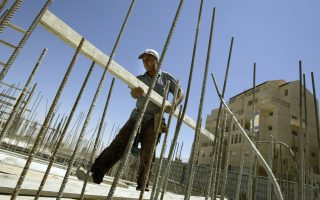 A worker helps construct a new apartment building at the West Bank Israeli settlement of Efrat, about 10 kms outside Jerusalem, Monday, Aug. 23, 2004. Israel announced plans Monday for more than 500 new housing units in the West Bank, following an apparent U.S. policy shift on Jewish settlements that has infuriated the Palestinians. (AP Photo/Oded Balilty)