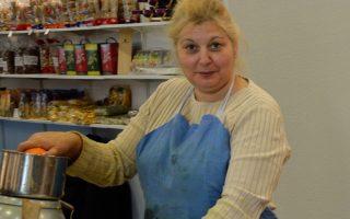 Με πλατύ χαμόγελο, η Ελένη Κωνσταντίνου από τη Σκάλα Λακωνίας στύβει πορτοκαλάδες στους επισκέπτες, που κάνουν μπροστά της ουρά.