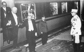 Αθήνα, 14 Μαΐου 1956. Σκηνή σε ύφος Μεσοπολέμου. Ο βασιλιάς Παύλος υποδέχεται στον Σταθμό Λαρίσης τον πρόεδρο της Ομοσπονδιακής Δημοκρατίας της Γερμανίας δόκτορα Τέοντορ Χόυς, τον οποίον υποβαστάζει ο υπουργός του των Εξωτερικών Χάινριχ φον Μπρεντάνο.