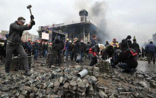 Πίσω από την ομάδα κρούσης των διαδηλωτών στην Ουκρανία υπάρχει ένα ολόκληρο δίκτυο υποστήριξης, έτσι ώστε όλη την ημέρα τα χαρακώματα να παραμένουν ζωντανά και ενεργά. Όπως ο κύριος της φωτογραφίας που σπάει σε μικρότερα κομμάτια τις πέτρες των πεζοδρομίων που έχουν κάποιοι άλλοι βγάλει. AFP PHOTO/GENYA SAVILOV