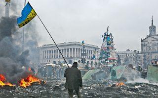 Διαδηλωτής βαδίζει στην πλατεία Ανεξαρτησίας του Κιέβου. Ο υπουργός Εξωτερικών της Πολωνίας, Ντόναλντ Τουσκ, δήλωσε, με επιφυλάξεις, ότι ο πρόεδρος Γιανουκόβιτς συμφώνησε «ότι θα διεξαχθούν φέτος προεδρικές και βουλευτικές εκλογές» και ότι θα συσταθεί «μια κυβέρνηση εθνικής ενότητας μέσα στις επόμενες 10 ημέρες».