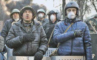Διαδηλωτές στα χαρακώματα, τραγουδούν τον εθνικό ύμνο της Ουκρανίας.