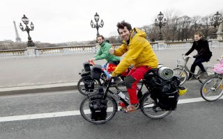 Simon Poniard (R) and Basile Pottier (L) start to cycle in Paris on their way to Beijing to mark the 50th anniversary of the start of Franco-Chinese diplomatic relations on January 27, 2014. The pair will travel through 10 countries along the legendary Silk Road, covering a distance of some 12,500 km. AFP PHOTO/THOMAS SAMSON