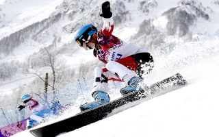 Russia's Alena Zavarzina (L) and Canada's Marianne Leeson compete in the Women's Snowboard Parallel Giant Slalom elimination run at the Rosa Khutor Extreme Park during the Sochi Winter Olympics on February 19, 2014.    AFP PHOTO / FRANCK FIFE