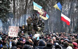 Πολίτες συγκεντρώθηκαν έξω από την ουκρανική Βουλή στο Κίεβο, την περασμένη Πέμπτη, ενώ μέσα οι βουλευτές ψήφιζαν τη νέα κυβέρνηση εθνικής ενότητας, που θα οδηγήσει τη χώρα σε προεδρικές εκλογές τον Μάιο.