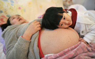Η πρώτη Κινεζούλα που θα έχει αδελφό. Η Li Yan αφήνει την κόρη της να ξαπλώσει πάνω στην κοιλιά της, λίγο πριν γεννήσει ένα υγιέστατο αγοράκι. Η οικογένεια της  Li Yan, είναι η πρώτη στη Κίνα που πήρε επίσημη άδεια να αποκτήσει και δεύτερο παιδί και σύμφωνα με κυβερνητικές πηγές, εκατομμύρια οικογένειες μέχρι το τέλος του χρόνου θα αποκτήσουν το ίδιο δικαίωμα, θέτοντας και επισήμως τέλος στην πολιτική του ενός παιδιού.Reuters