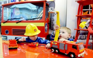 Young  Maurice and Pascal play with fire fighter toys at the International Toy Fair in Nuremberg, southern Germany, on January 28, 2014. The specialised trade fair runs from January 29 to February 3, 2014. AFP PHOTO / CHRISTOF STACHE