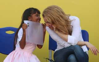 A girl talks to Colombia's pop star Shakira at a the inauguration of a school funded by her foundation