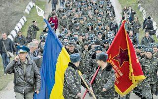 Ουκρανοί στρατιώτες με σημαίες την ώρα που φεύγουν από το αεροδρόμιο του Μπελμπέκ.
