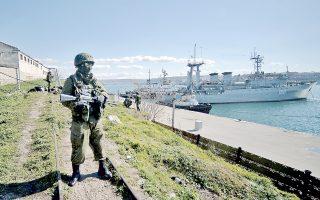 Ρώσος στρατιώτης φυλάει σκοπιά στο λιμάνι της Σεβαστούπολης, όπου βρίσκεται ο ναύσταθμος του ρωσικού στόλου της Μαύρης Θάλασσας. Πίσω του διακρίνεται το ουκρανικό πλοίο «Σλαβούτιτς». Ρωσικές δυνάμεις κατέλαβαν χθες δύο βάσεις πυραύλων του ουκρανικού στρατού στη Χερσόνησο της Κριμαίας.