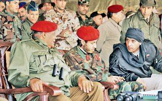 Ο Σααντί Καντάφι  (στο κέντρο) παρακολουθεί μαζί με τον αδελφό του Χάνιμπαλ (δεξιά) στρατιωτικές ασκήσεις τον Σεπτέμβριο του 2011.