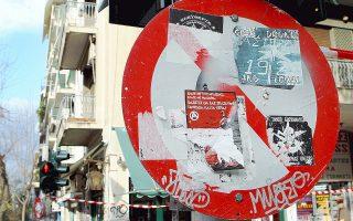 Παραποιημένη πινακίδα της Τροχαίας στην πλατεία Εξαρχείων, καλυμμένη από αυτοκόλλητα και σπρέι.