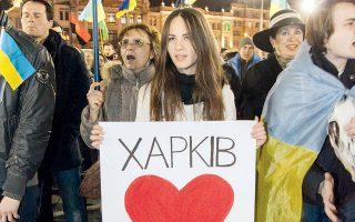 Μια νεαρή γυναίκα κρατάει πλακάτ στο οποίο αναγράφεται «Το Χάρκοβο αγαπά την Κριμαία». Δίπλα της, φιλο-Ουκρανοί ακτιβιστές τραγουδούν τον εθνικό ύμνο.