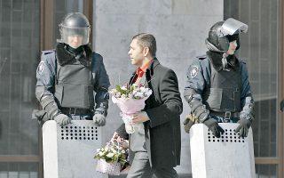 Ενας άνδρας κρατάει ένα μπουκέτο λουλούδια καθώς αστυνομικοί φρουρούν κυβερνητικό κτίριο στο Ντόνετσκ της Ουκρανίας.