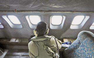 Μέλος του πληρώματος αεροσκάφους έρευνας της Βασιλικής Πολεμικής Αεροπορίας της Μαλαισίας κοιτάζει προσεκτικά από το φινιστρίνι ελπίζοντας να βρει κάτι που θα λύσει το μυστήριο της εξαφάνισης της πτήσης ΜΗ370.