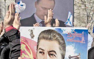 Ηλικιωμένη κρατάει ημερολόγιο με τη φιγούρα του Ιωσήφ Στάλιν, ενώ παρακολουθεί από γιγαντοοθόνη την ομιλία του Πούτιν, στη Σεβαστούπολη.
