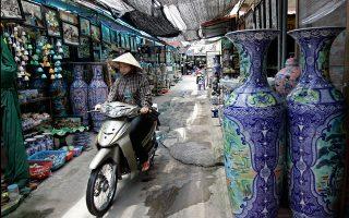 Γυναίκα με μοτοποδήλατο σε παραδοσιακή αγορά του σύγχρονου Βιετνάμ. «Ελπίζω να κάνω τους φοιτητές μου», γράφει η Νάταλι Μπακόπουλος, «να αντιλαμβάνονται στοχαστικά τον κόσμο γύρω τους».