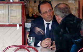 O Φρανσουά Ολάντ σε καφέ μετά την ψηφοφορία στον πρώτο γύρο των γαλλικών δημοτικών εκλογών. Εξω από το τζάμι τον πολιορκούν οι φωτογράφοι.