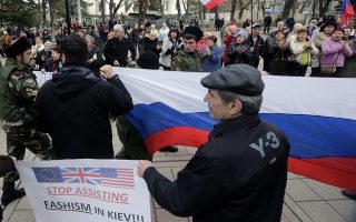 epa04112273 Pro-Russian activists hold a Russian flag during a pro-Russian rally near the Crimea's parliment in Simferopol, Ukraine, 06 March 2014. The Crimea's parliment moved the date of all-Crimean referendum on the status of the Autonomous Republic of Crimea to March 16.  EPA/MAXIM SHIPENKOV