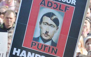«Αδόλφε Πούτιν, κάτω τα χέρια από την Ουκρανία», γράφει το πανό, από διαδήλωση στο Κίεβο στις 23 Μαρτίου.