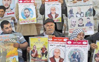 Συγγενείς Παλαιστινίων που κρατούνται σε ισραηλινές φυλακές διαδηλώνουν μπροστά από τα γραφεία του Ερυθρού Σταυρού στη Ραμάλα της Δυτικής Οχθης, ζητώντας την απελευθέρωση των οικείων τους.