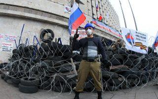 Φιλορώσος διαδηλωτής ποζάρει στο οδόφραγμα, μπροστά από το κυβερνείο του Ντόνετσκ.