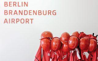 Κόκκινα προστατευτικά κράνη περιμένουν τους επισκέπτες-δημοσιογράφους, σε αίθουσα του αεροδρομίου Σόνεφελντ του Βερολίνου.