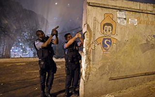 Προς την κατεύθυνση της παραγκούπολης Παβαοζίνια, στα υψώματα πάνω από την παγκοσμίως διάσημη παραλία Κοπακαμπάνα του Ρίο, σημαδεύουν με τα όπλα τους οι αστυνομικοί, αντιμέτωποι με τους οργισμένους κατοίκους της συνοικίας, που διαμαρτύρονταν για τη δολοφονία γείτονά τους από τις Αρχές.