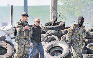Ενοπλοι φιλορώσοι αυτονομιστές σε οδόφραγμα, στην πόλη Σλαβιάνσκ. Πέντε ομοϊδεάτες τους σκοτώθηκαν χθες από πυρά Ουκρανών στρατιωτών σε σημείο ελέγχου, στα περίχωρα της πόλης, στην Ανατολική Ουκρανία.