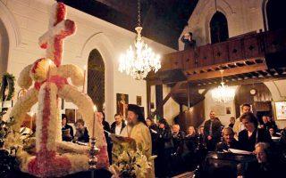 Mεγάλη Παρασκευή στην ορθόδοξη εκκλησία της Aγίας Φωτεινής Σμύρνης με τον Eλληνα ιερέα να αναγινώσκει το Aγιον Eυαγγέλιο μπροστά στον ανθοστόλιστο Eπιτάφιο και...