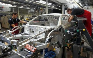 Workers assemble a new Audi R8 car body in the automotive welding and assembly lines hall of the German car manufacturer's plant in Neckarsulm July 3, 2013. REUTERS/Michaela Rehle