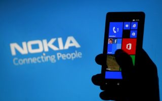 A woman poses with a Nokia Lumia smartphone in the central Bosnian town of Zenica, in this May 6, 2013 file illustration photograph. Microsoft Corp said on September 3, 2013 it would buy Nokia's mobile phone business for 5.44 billion euros ($7.2 billion), and the Finnish firm said its CEO, Stephen Elop, would join Microsoft when the transaction closed. REUTERS/Dado Ruvic (BOSNIA AND HERZEGOVINA - Tags: BUSINESS TELECOMS SCIENCE TECHNOLOGY)