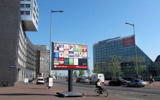 Ποδηλάτισσα περνάει μπροστά από προεκλογικές αφίσες, αναρτημένες σε ειδική προθήκη, στη συνοικία Βεστερντοκσντάικ του Αμστερνταμ.
