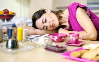 woman asleep on kitchen table during breakfast