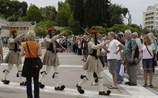 Κάποιοι από τα εκατομμύρια των τουριστών που έρχονται στην Ελλάδα παρακολουθούν και φωτογραφίζουν την αλλαγή φρουράς στο Μνημείο του Αγνωστου Στρατιώτη.