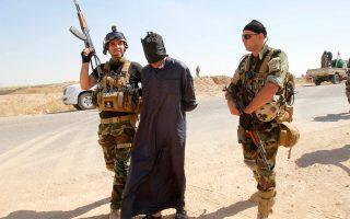 Ανδρες των κουρδικών δυνάμεων ασφαλείας μεταφέρουν ύποπτο για συμμετοχή στη σουνιτική, εξτρεμιστική οργάνωση ISIS, στο Κιρκούκ.