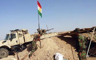 Κούρδοι στρατιώτες υψώνουν τη σημαία της αυτόνομης κουρδικής περιοχής, στον δρόμο που συνδέει το Κιρκούκ με την Τικρίτ.