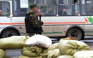 Ενα λεωφορείο περνά καθώς ένας ένοπλος φιλορώσος εξτρεμιστής πραγματοποιεί ελέγχους στο Ντονέτσκ της ανατολικής Ουκρανίας.