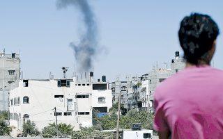 Την έκρηξη βόμβας ισραηλινού αεροσκάφους σε κατοικημένη περιοχή της Γάζας παρακολουθεί αυτός ο Παλαιστίνιος.